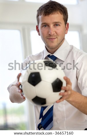 Handsome business man indoors holding a football - stock photo