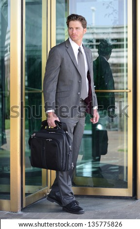 Handsome Business Man Leaving Building through Revolving Doors - stock photo