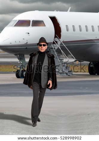 Handsome business man near a private jet wearing a hat.