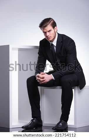 Handsome business man sitting on a white table holding his hands crossed while looking at the camera. - stock photo