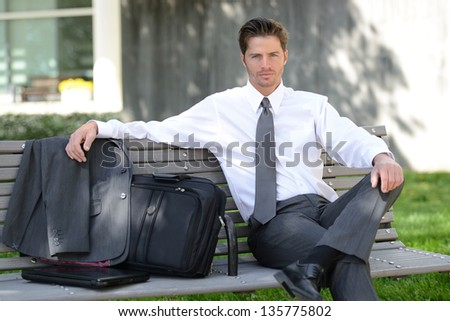 Handsome Business Man Sitting on Park Bench - stock photo