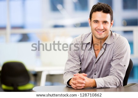 Handsome business man smiling at the office - stock photo