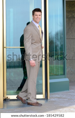 Handsome Business Man Smiling Leaving through Revolving Doors  - stock photo