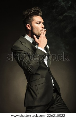 Handsome business man smoking a cigarette while looking away from the camera, side view.
