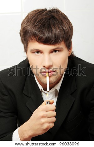Handsome business man smoking in bathroom