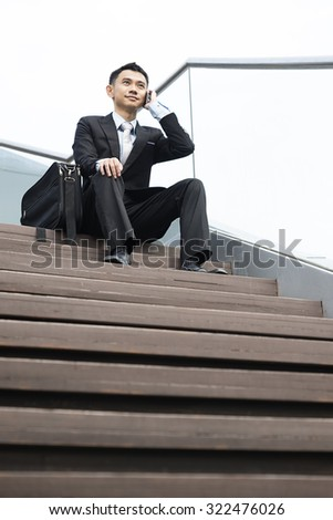 handsome business man speaking mobile phone at his company office building, model is a asian male - stock photo