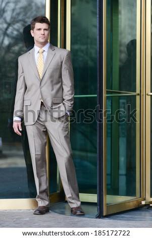 Handsome Business Man Standing Beside Revolving Doors  - stock photo