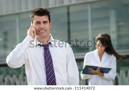 Handsome business man talking by cellphone while his secretary is taking notes