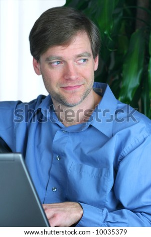 Handsome business man using laptop while relaxing on couch