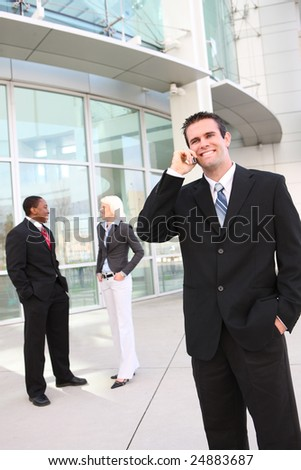 Handsome Business Man with team at the office building - stock photo