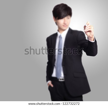 handsome Business man writing with marker pen in the air isolated on gray background, great for you add any text or graph - stock photo