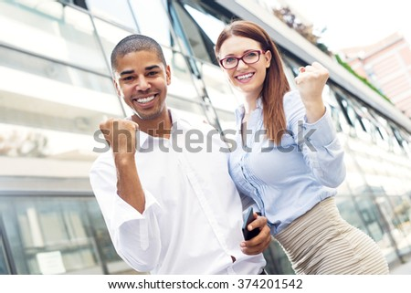 Handsome businessman and his partner holding their fists up, smiling and looking at camera. - stock photo