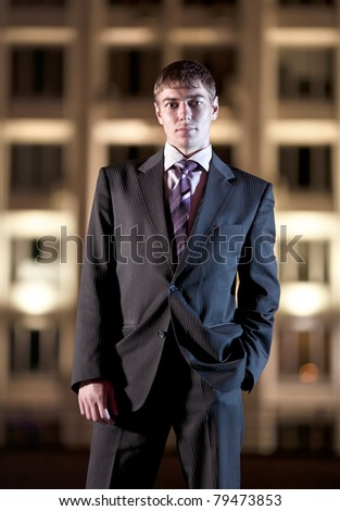 Handsome businessman and light building at night city in the background - stock photo