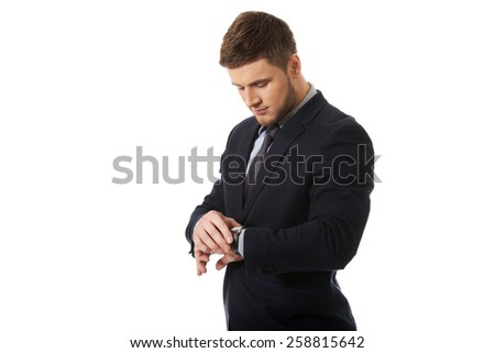 Handsome businessman checking time on his wrist watch. - stock photo