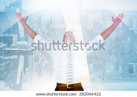 Handsome businessman cheering with arms up against low angle view of skyscrapers - stock photo