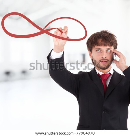 Handsome businessman drawing infinity symbol - stock photo