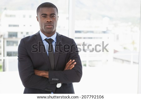 Handsome businessman frowning at camera in his office - stock photo