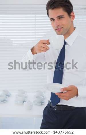 Handsome businessman having a coffee during the break