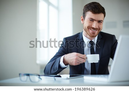 Handsome businessman having tea or coffee in office - stock photo