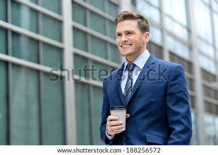 Handsome businessman holding a cup of coffee looking away - stock photo