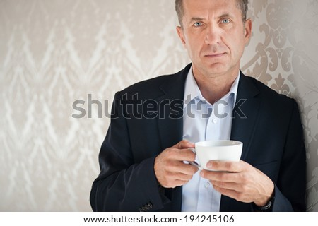 Handsome businessman holding cup of coffee - stock photo