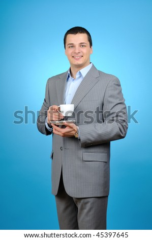 Handsome businessman holding cup of tea on blue background - stock photo