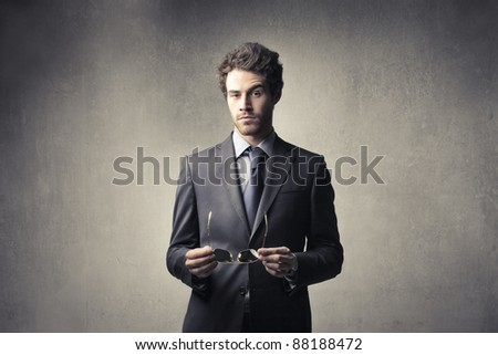 Handsome businessman holding eyeglasses - stock photo