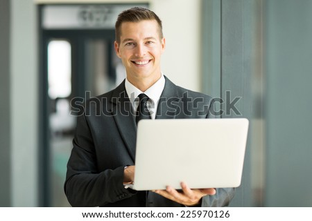handsome businessman holding laptop in office - stock photo