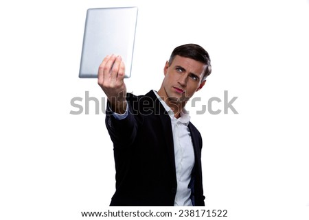 Handsome businessman holding tablet computer and looking at it - stock photo