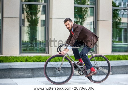 Handsome businessman in a jacket riding on his bicycle on city streets. The concept of the modern lifestyle of young men - stock photo