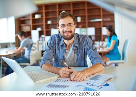 Handsome businessman in casual looking at camera in office on background of his partners