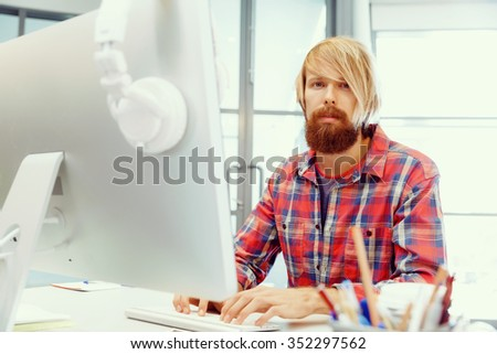 Handsome businessman in casual wear working in office