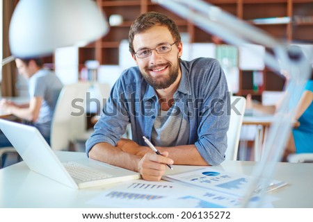 Handsome businessman in casual working in office on background of his partners