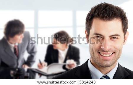 Handsome Businessman in front of his colleagues - stock photo