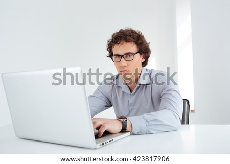 Handsome businessman in glasses working on laptop computer in office and looking at camera