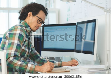 Handsome businessman in glasses writing down his ideas