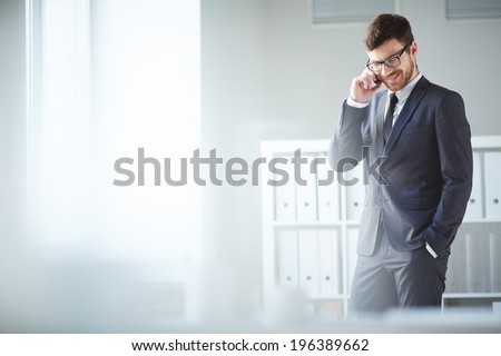 Handsome businessman in suit and eyeglasses speaking on the phone in office - stock photo