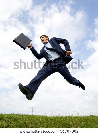 Handsome businessman in suit leaping over green grass with cloudy sky at background - stock photo