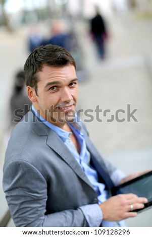 Handsome businessman in town using tablet - stock photo