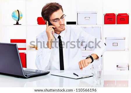 Handsome businessman is calling on his cell phone at the office. - stock photo