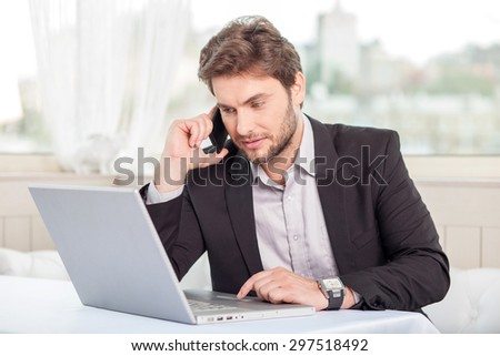 Handsome businessman is sitting at the table in restaurant and talking on the phone. He is looking at his notebook with concentration - stock photo