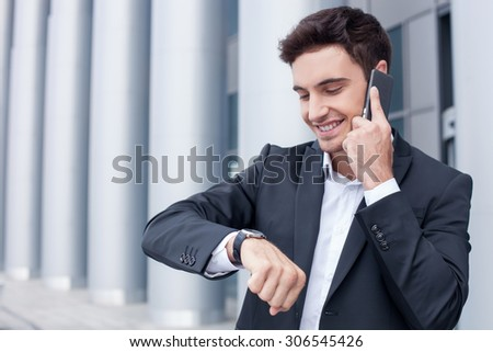 Handsome businessman is standing near his office and communicating on the phone. He is arranging the meeting with his business partner and smiling. The man is looking at his watch - stock photo