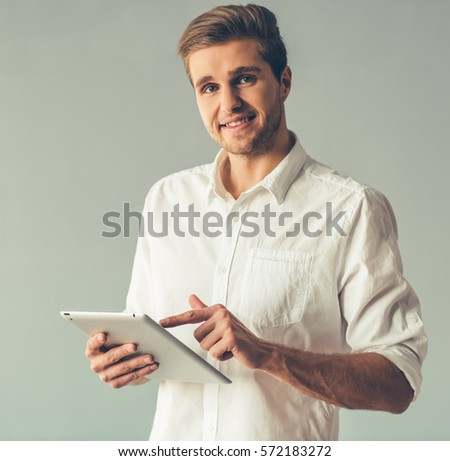 Handsome businessman is using a digital tablet, looking at camera and smiling, on gray background