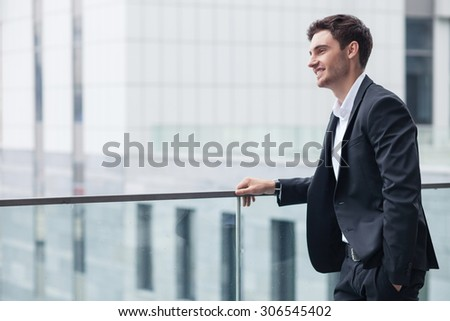 Handsome businessman is waiting for his client. He is standing near a building and putting his arm in pocket. The worker is looking forward happily and smiling. Copy space in left side - stock photo
