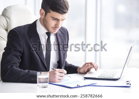 Handsome businessman is working with laptop in office. - stock photo