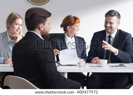 Handsome businessman joking with new applicant and other employers during job interviewHandsome businessman joking with new applicant and other employers during job interview - stock photo
