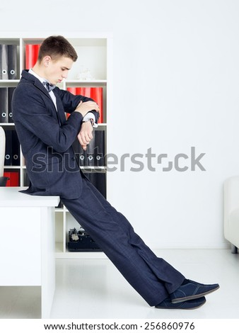 handsome businessman looking at watch in his office - stock photo