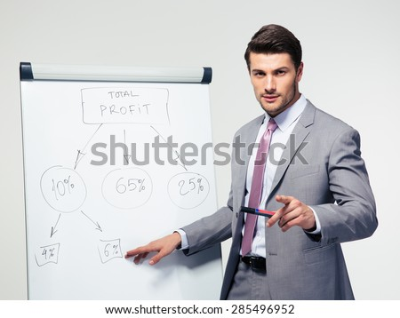 Handsome businessman making presentation on flipchart over gray background. Looking at camera  - stock photo