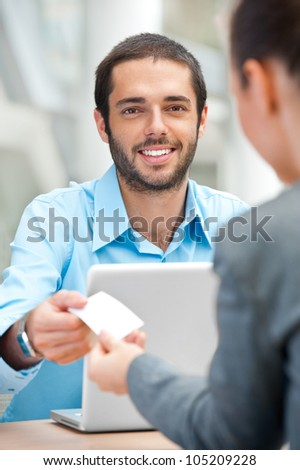 Handsome businessman offering his visiting card to partner