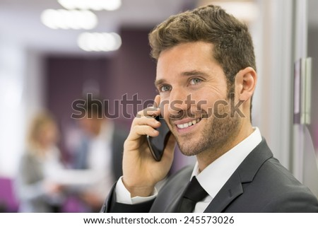 Handsome businessman on mobile phone in modern office - stock photo